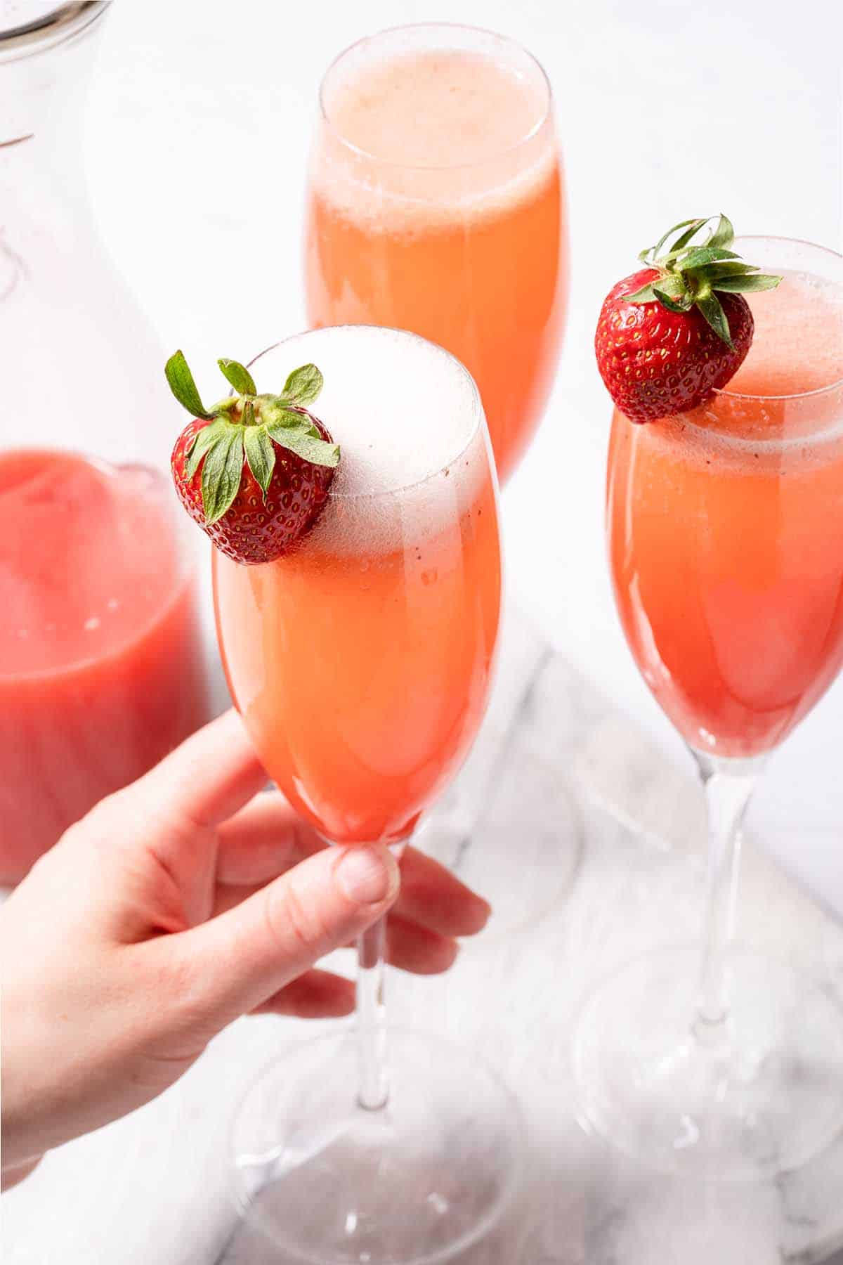 hand holding strawberry mimosa with two other mimosas on the side