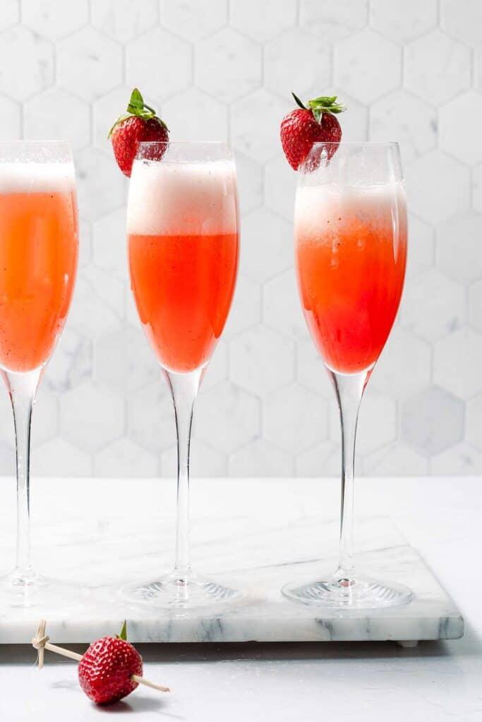 three glasses of strawberry mimosas