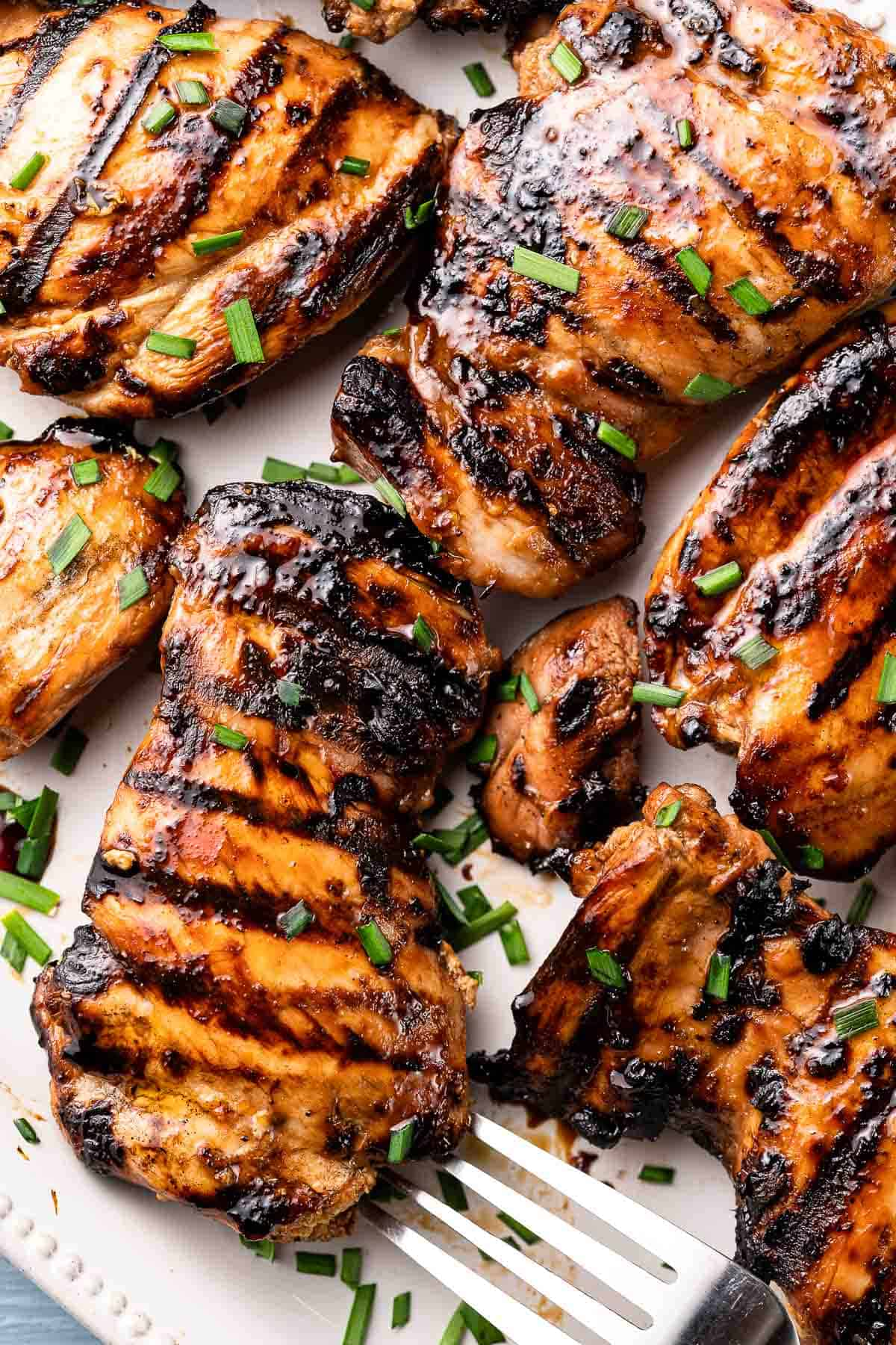 grilled balsamic chicken on white plate with fork