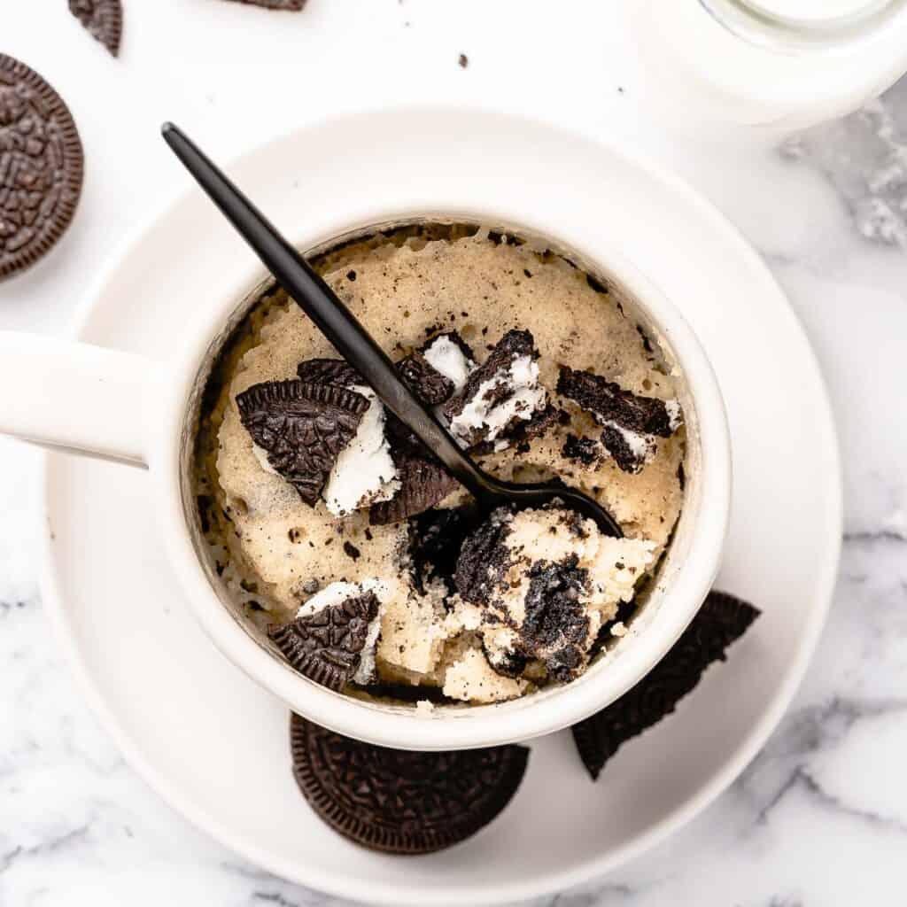Oreo mug cake in white mug with black spoon