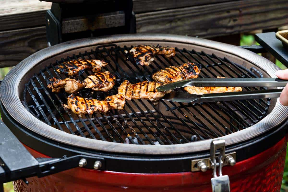 tongs flipping chicken on grill