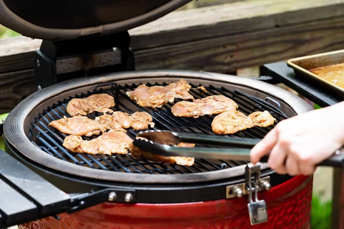 tongs placing chicken on grill