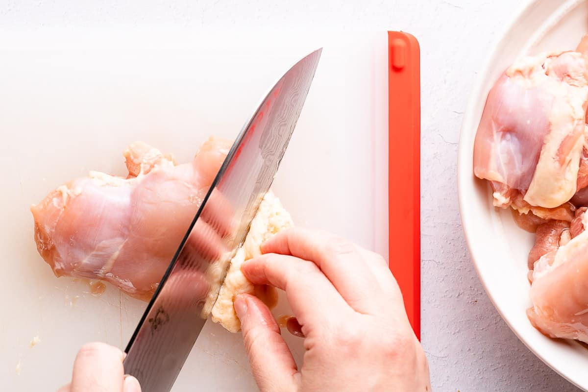 knife trimming excess fat from chicken thigh
