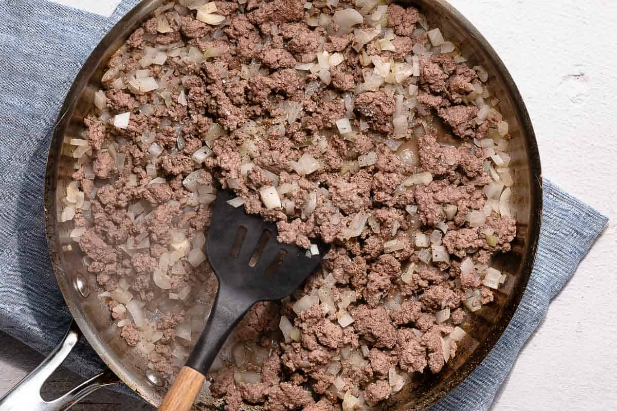 cooked ground beef and onions in skillet