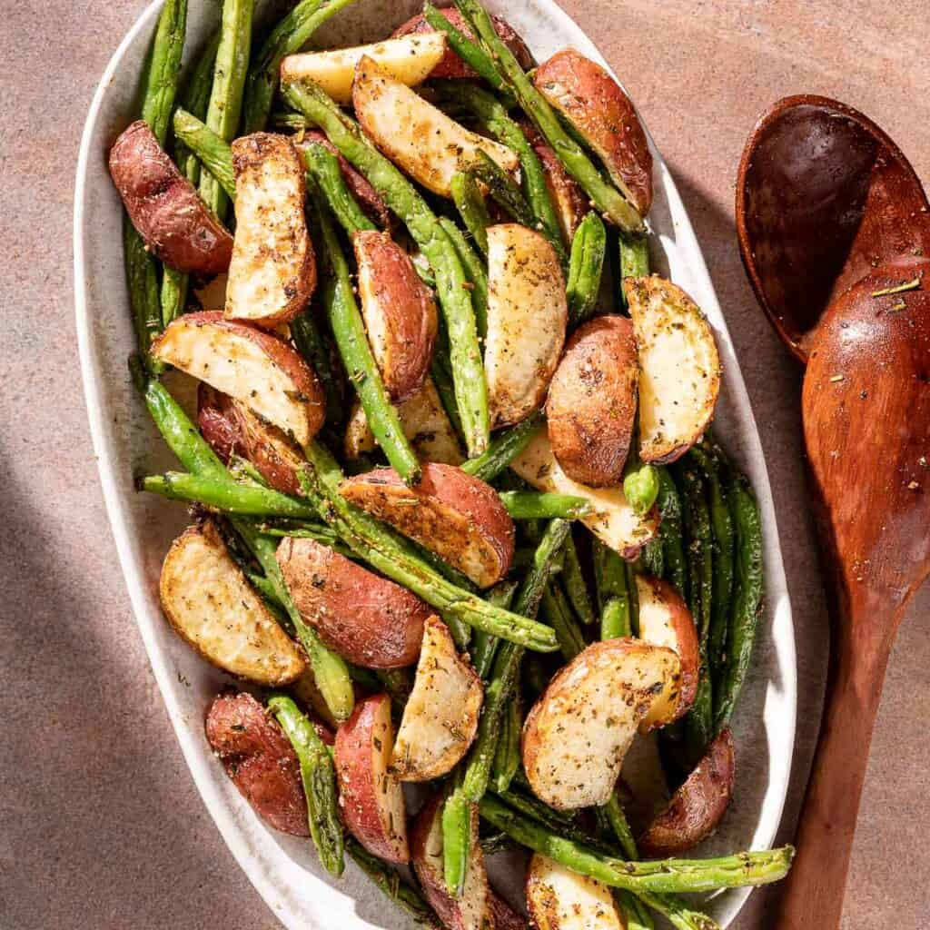 potatoes and green beans on platter with serving spoon on the side
