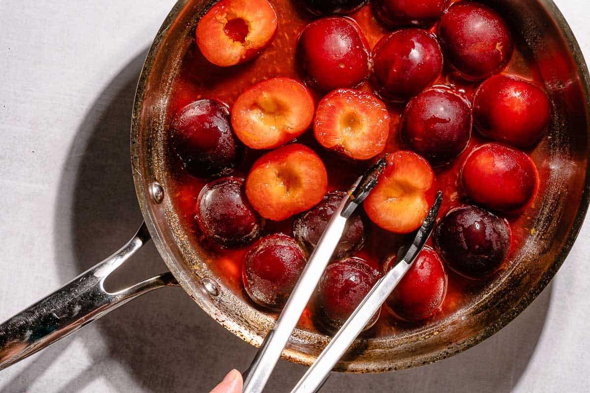 tongs flipping plum half in pan