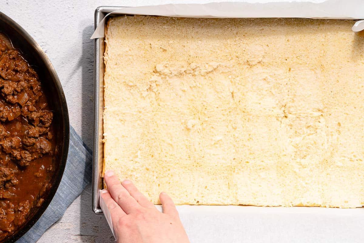 hands placing bottom half of slider buns in pan