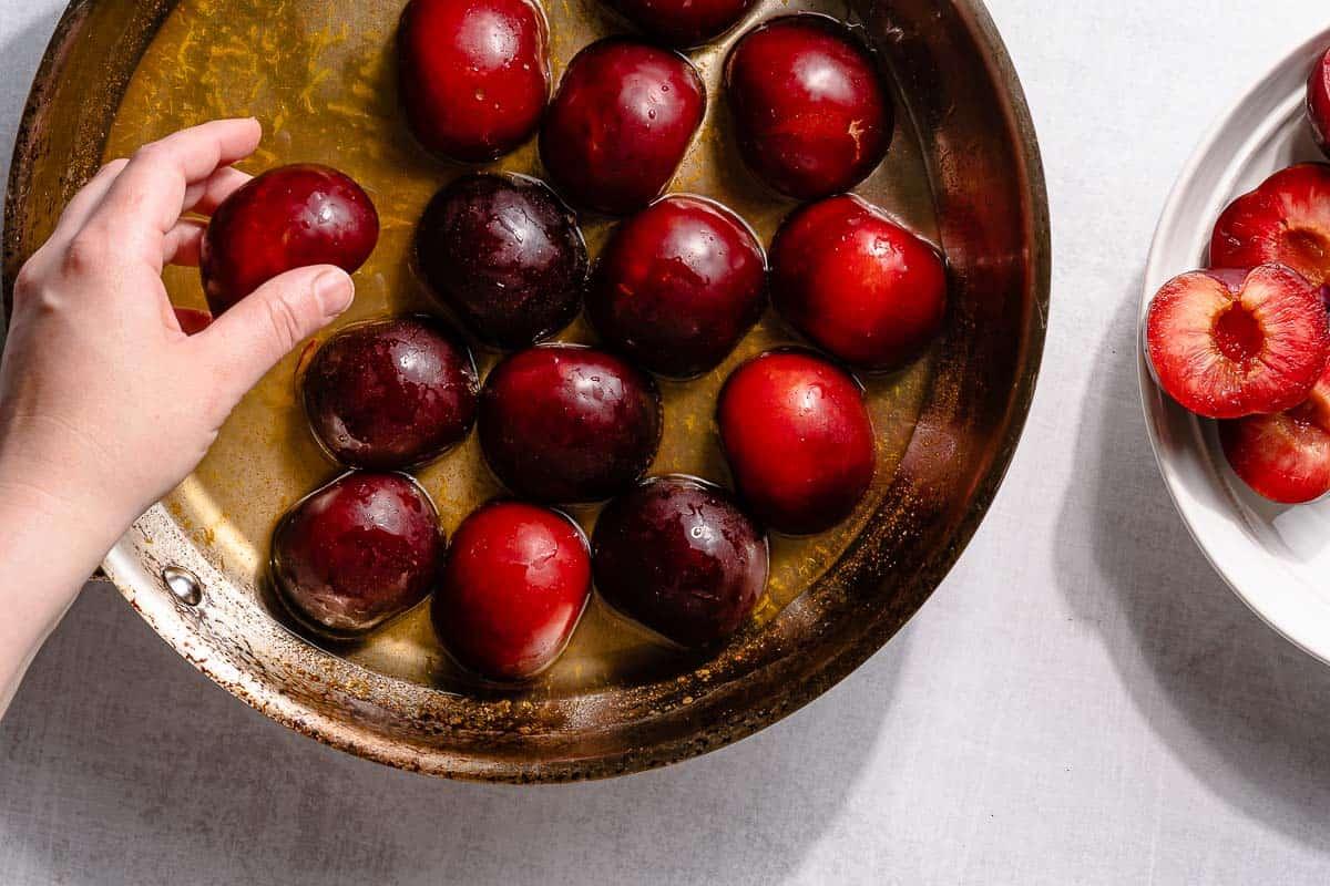 hand placing plum halves in pan
