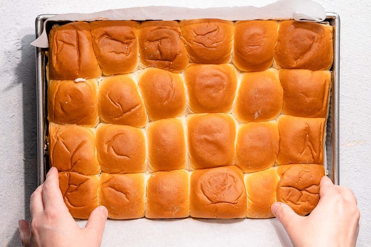 hands placing top half of slider buns in pan