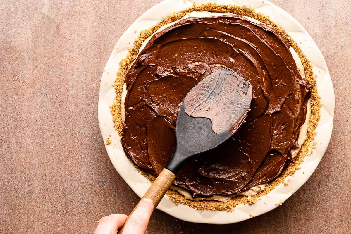 spatula spreading ganache on top of pie