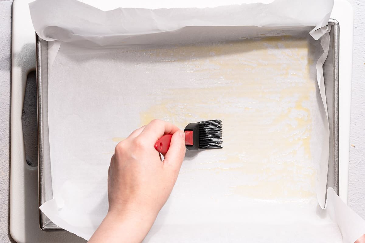 pastry brush spreading melted butter on parchment paper in pan