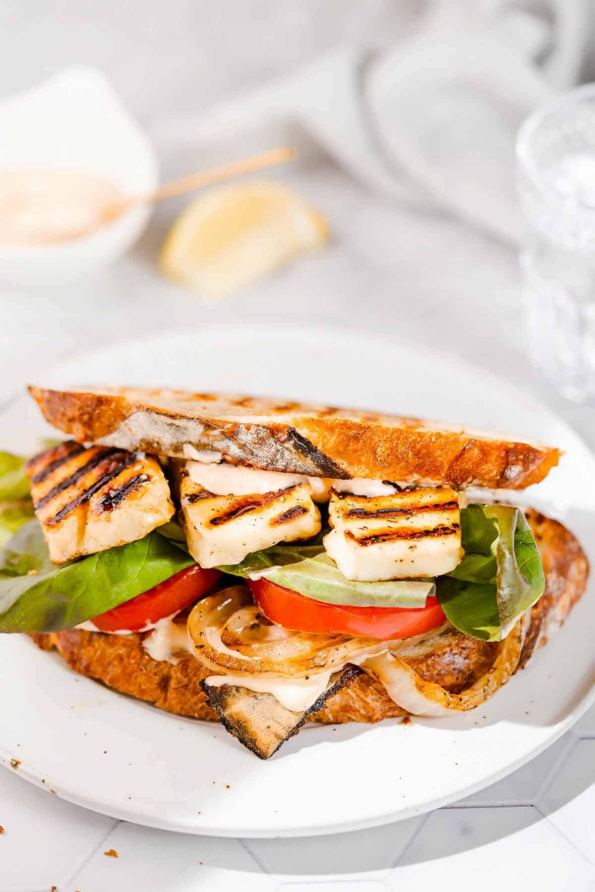 halloumi sandwich on white plate with lemon and mayo on the side