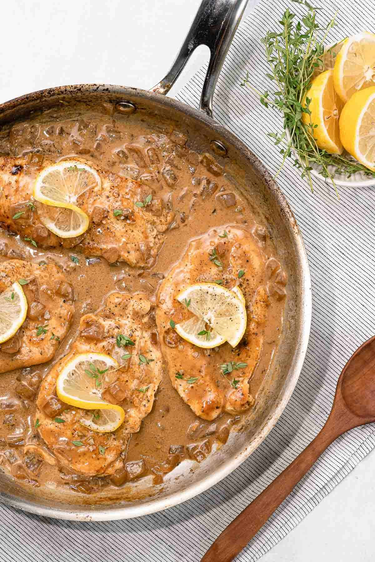 lemon butter chicken in pan with lemons and spoon on the side