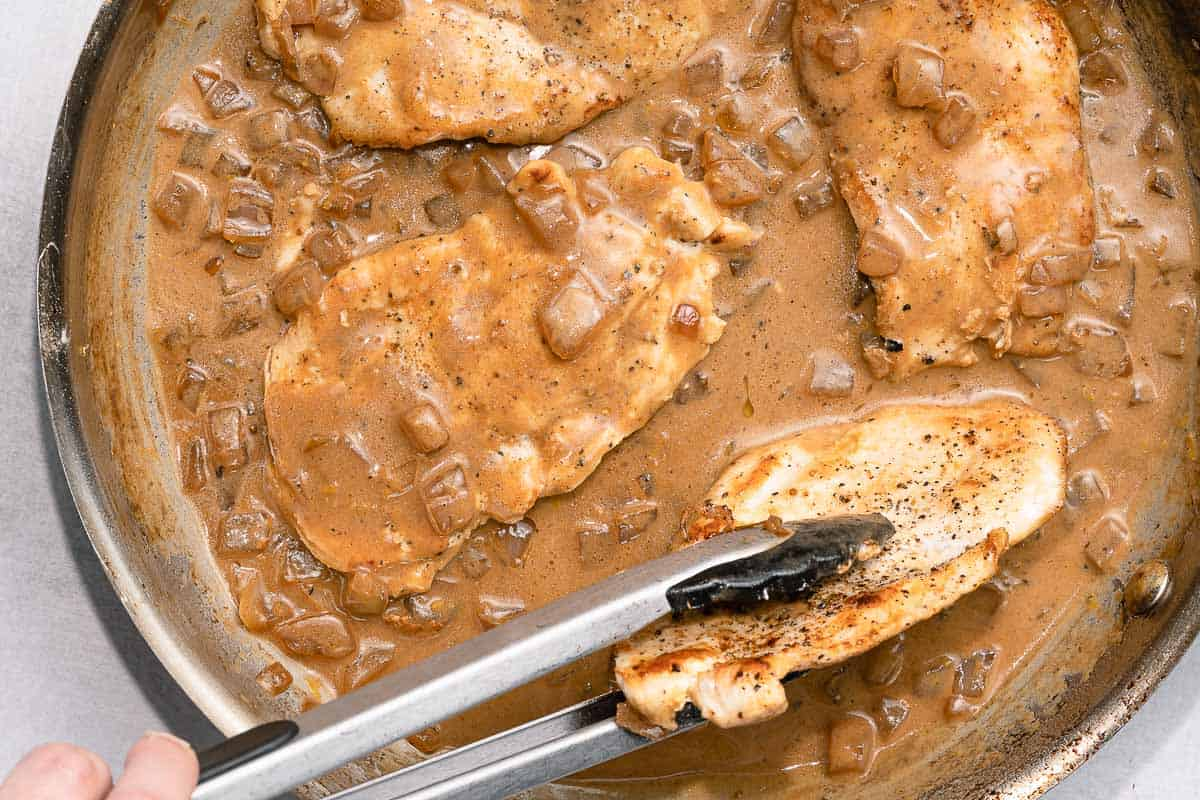 tongs placing cooked chicken breasts into sauce in pan