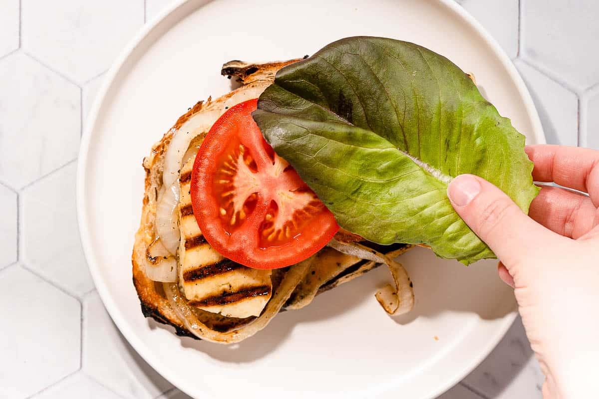 hand placing lettuce on halloumi sandwich
