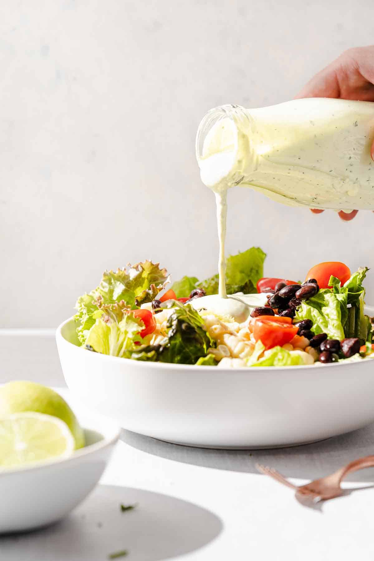 dressing being poured onto a salad