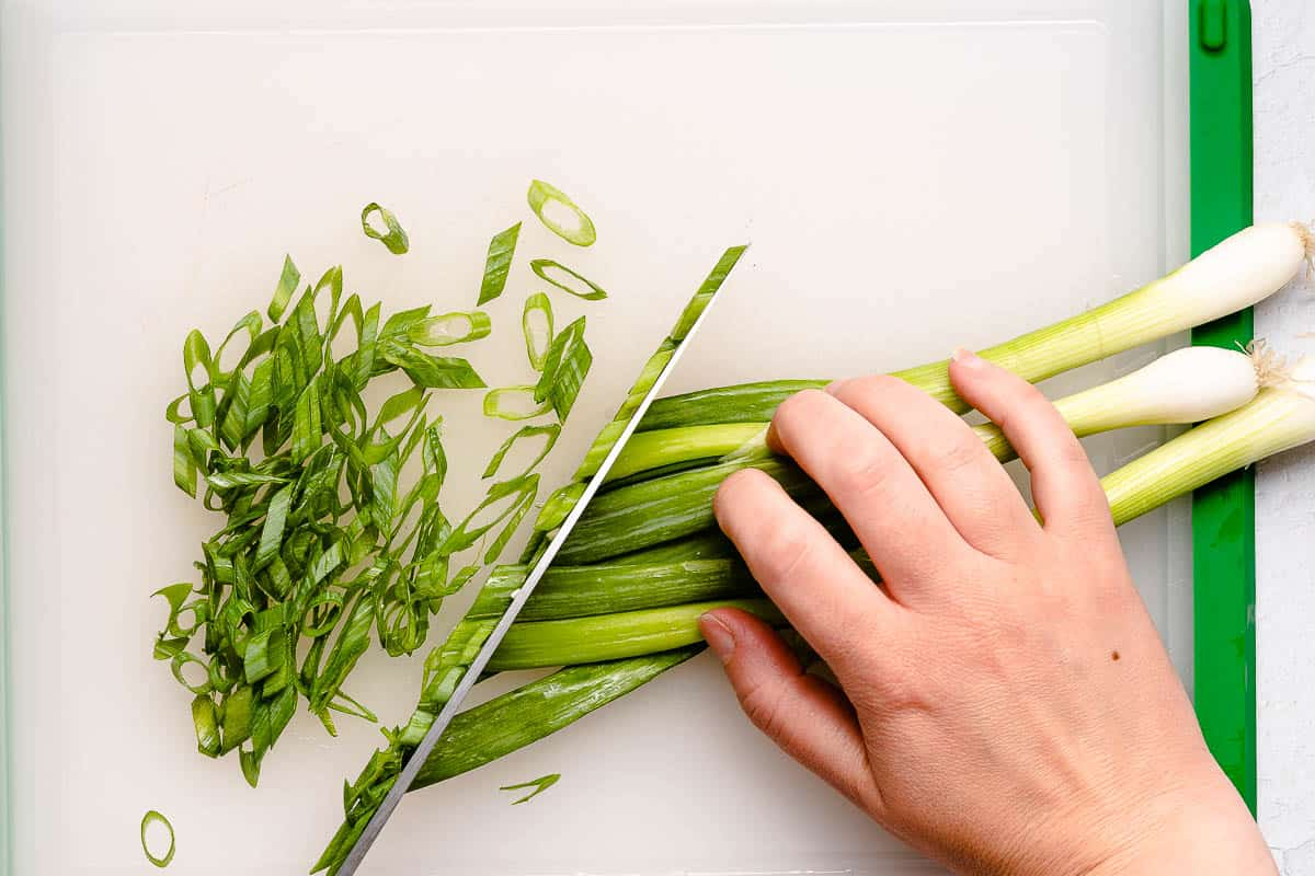 green onion tops being chopped on cutting board