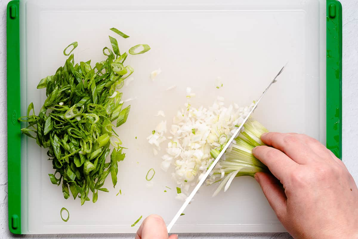white part of green onion being finely chopped on cutting board