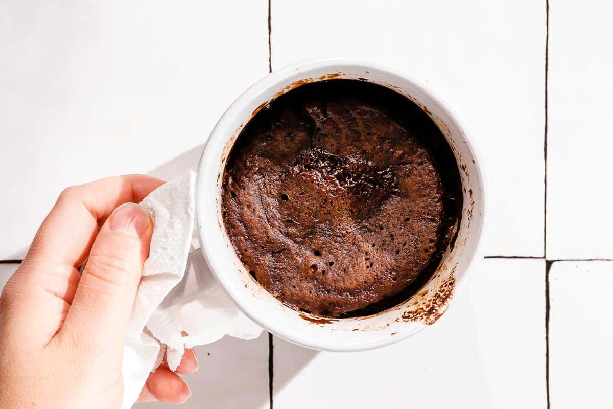 hand holding cooked mug cake with paper towel