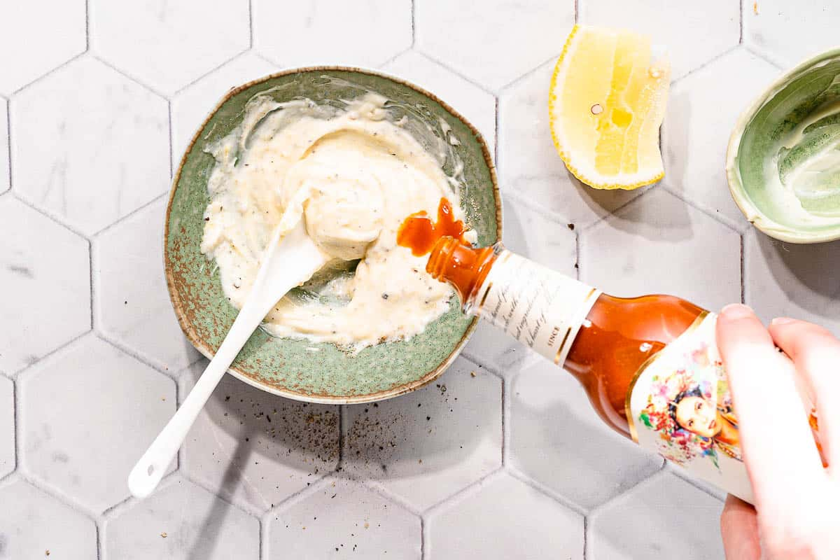 hot sauce being added into mayo in small bowl