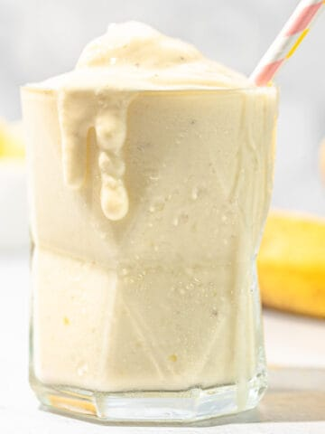 pineapple banana smoothie in glass with bananas
