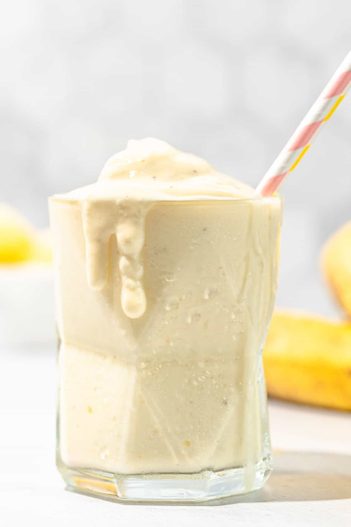pineapple banana smoothie in short glass with pink straw