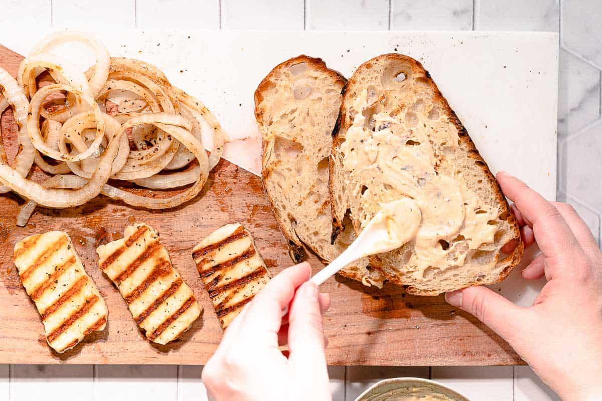 mayo being spread on grilled bread with onions and halloumi on the side