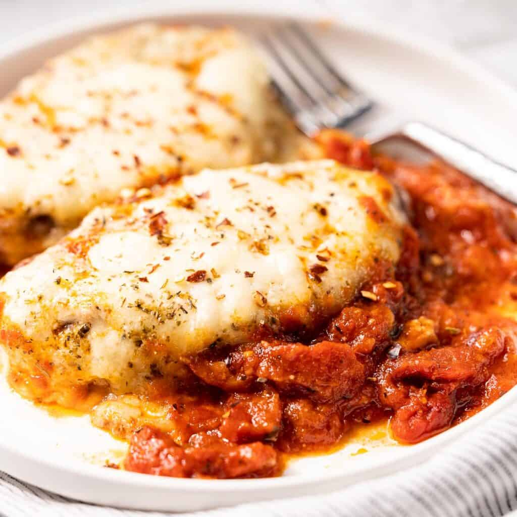 two stuffed sausages on plate with tomato sauce on the side
