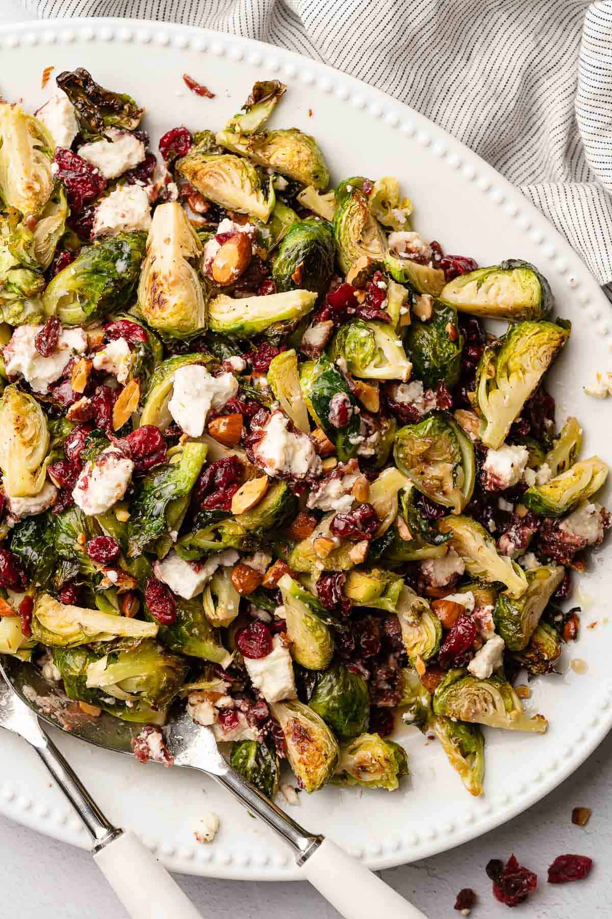brussels sprouts salad with cranberries on white platter with napkin in background