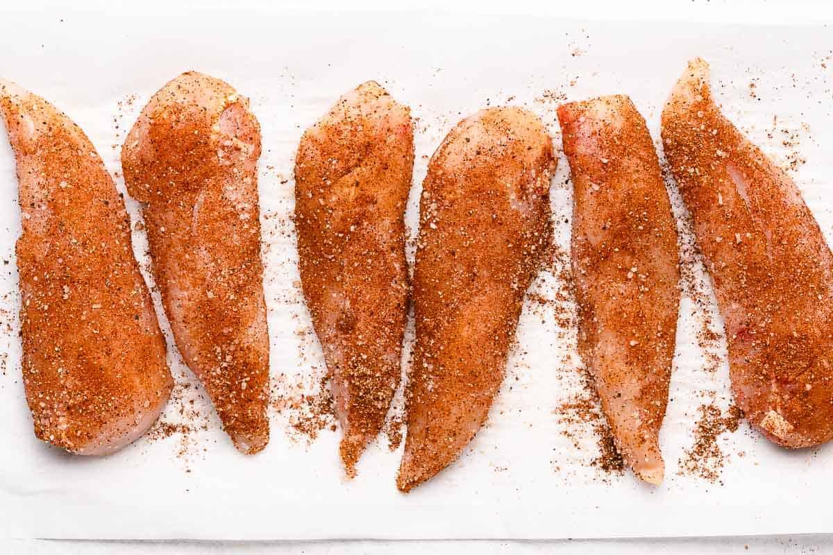 seasoned chicken tenders on parchment paper