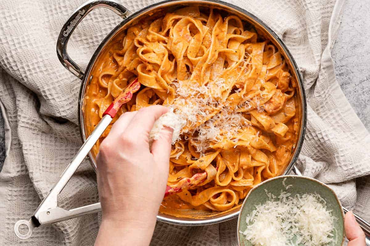 shredded Parmesan being sprinkled into finished pasta dish