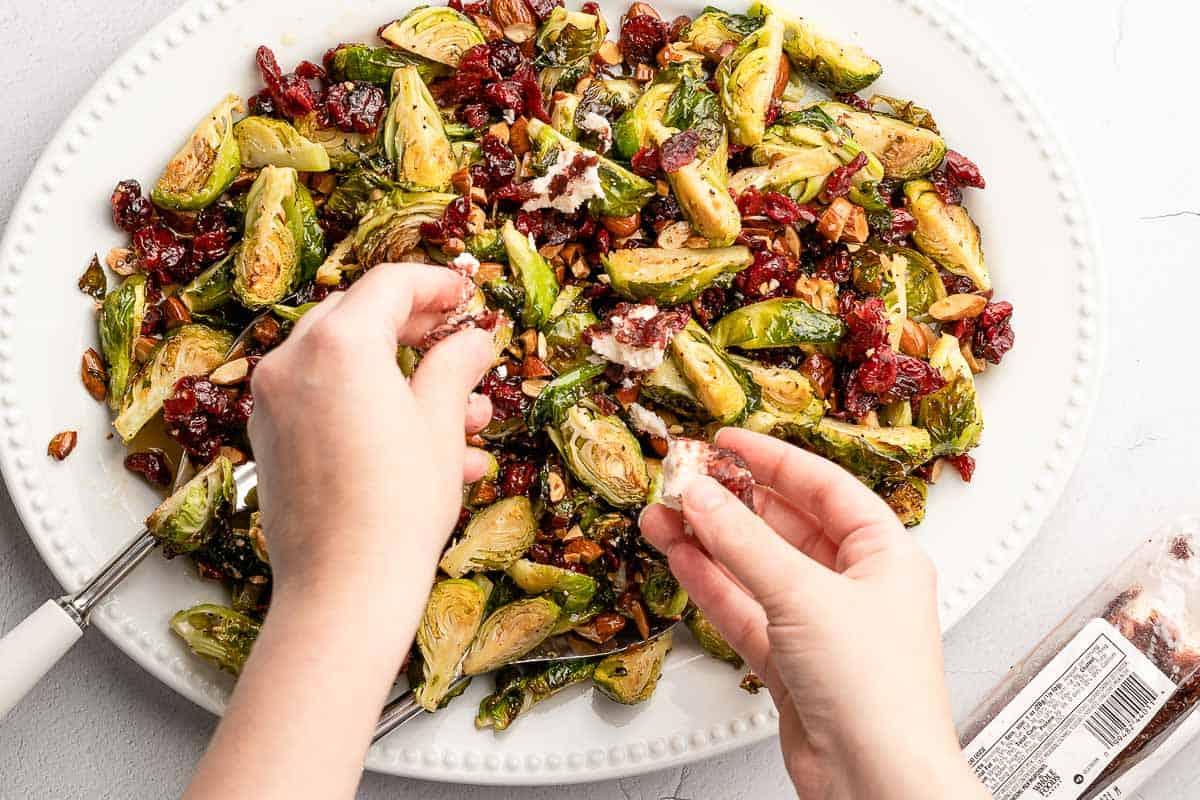 hands crumbling cheese overtop salad on platter