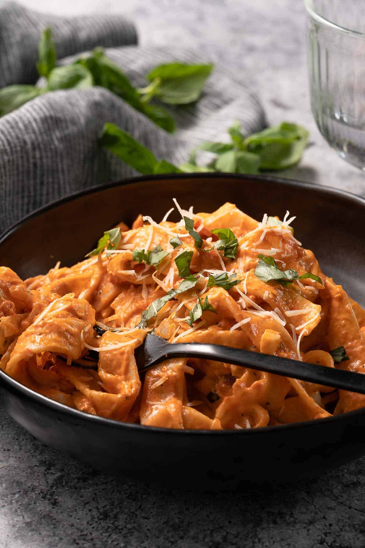bowl of creamy tomato pasta in black bowl with fork