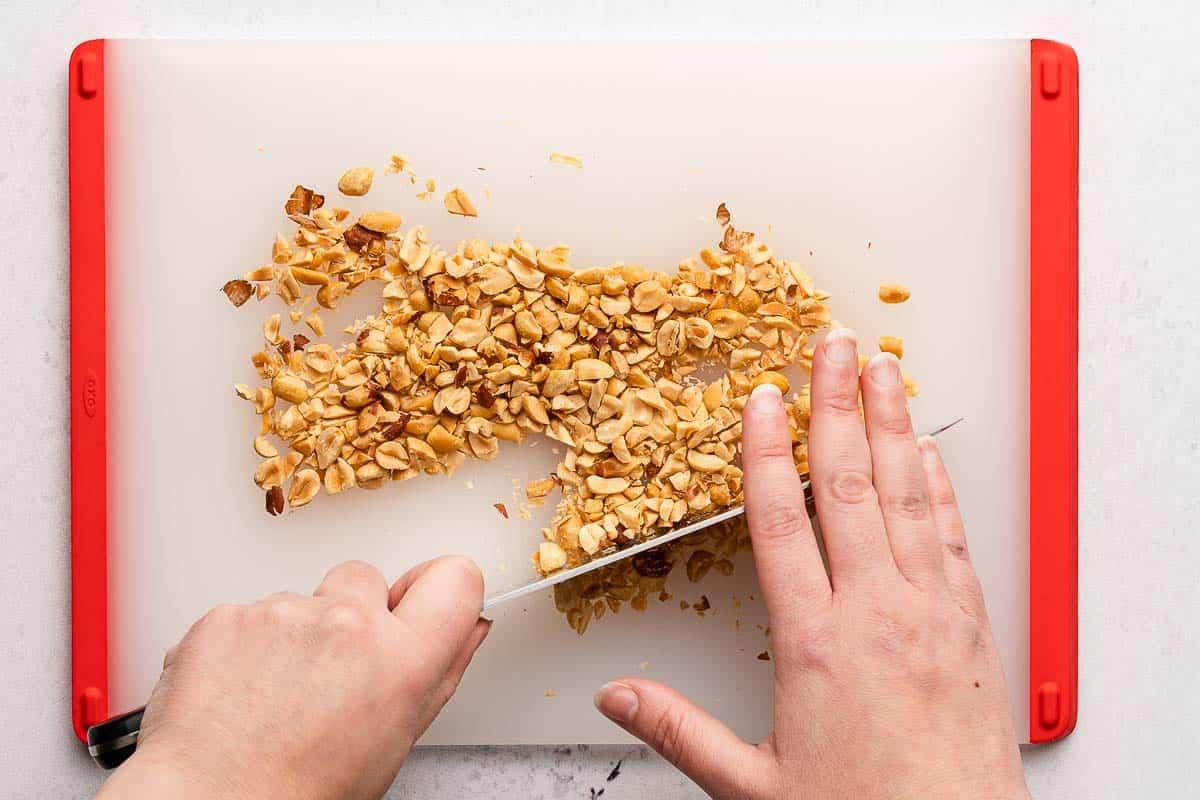 knife chopping peanuts on cutting board