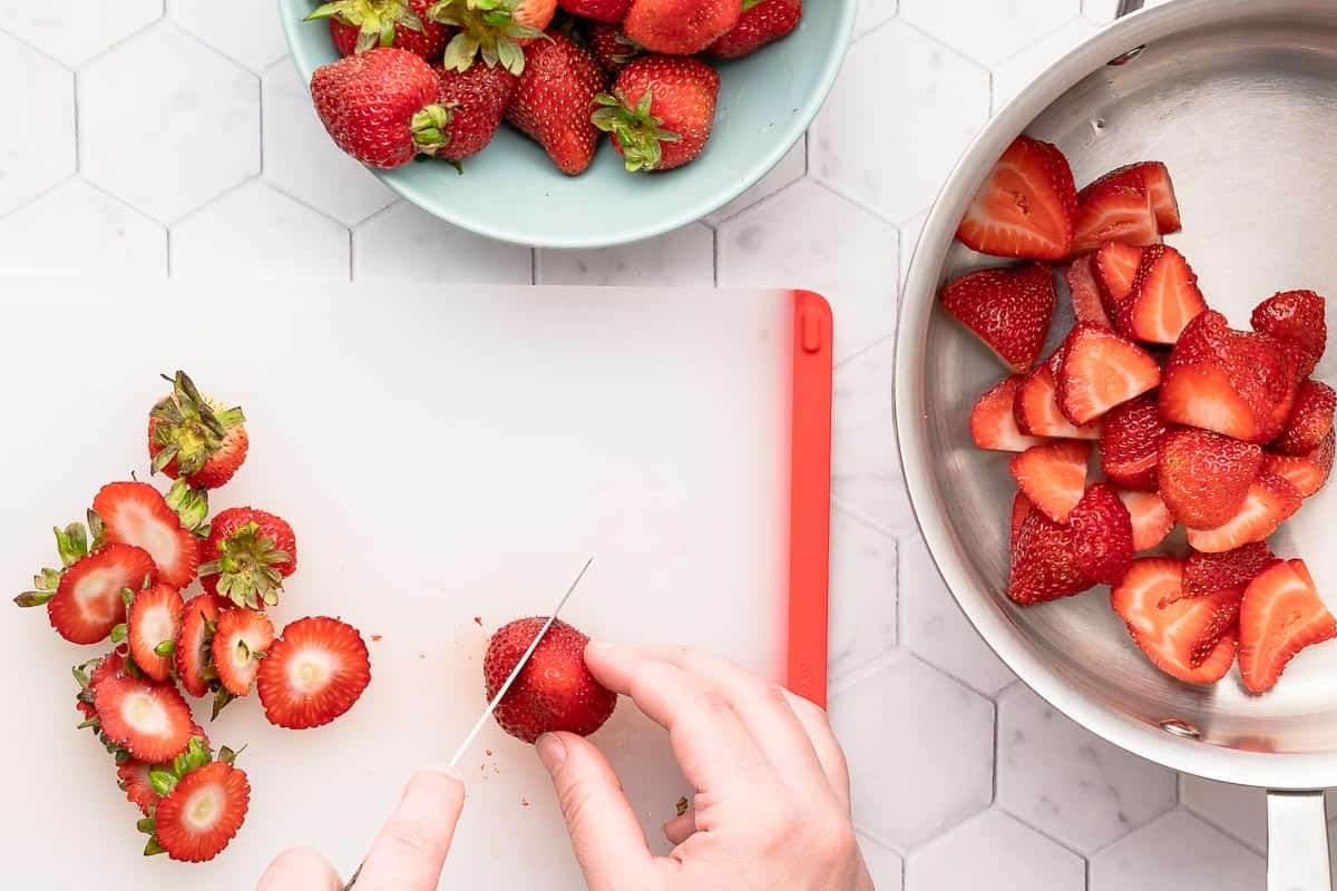 hands slicing strawberries on cutting board with pan on the side