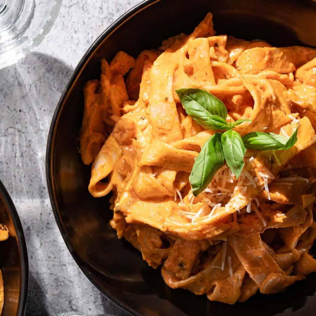 creamy tomato pasta in black bowl