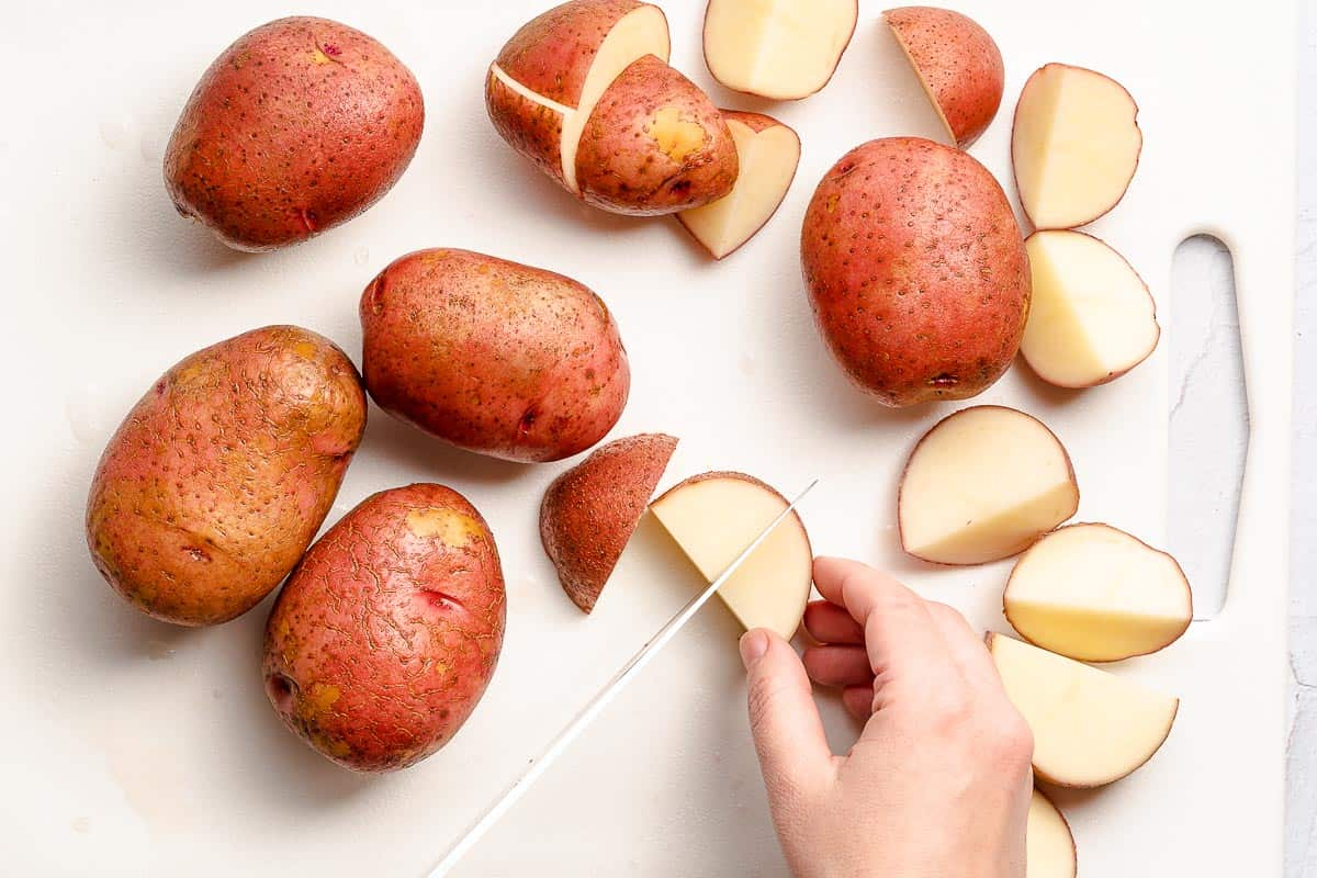 potatoes being cut into chunks