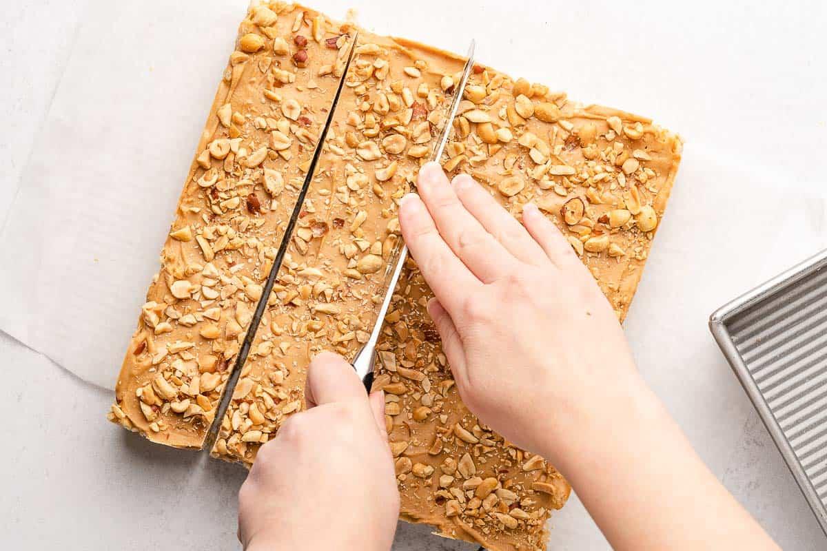 large knife cutting peanut butter rice krispie treats into strips