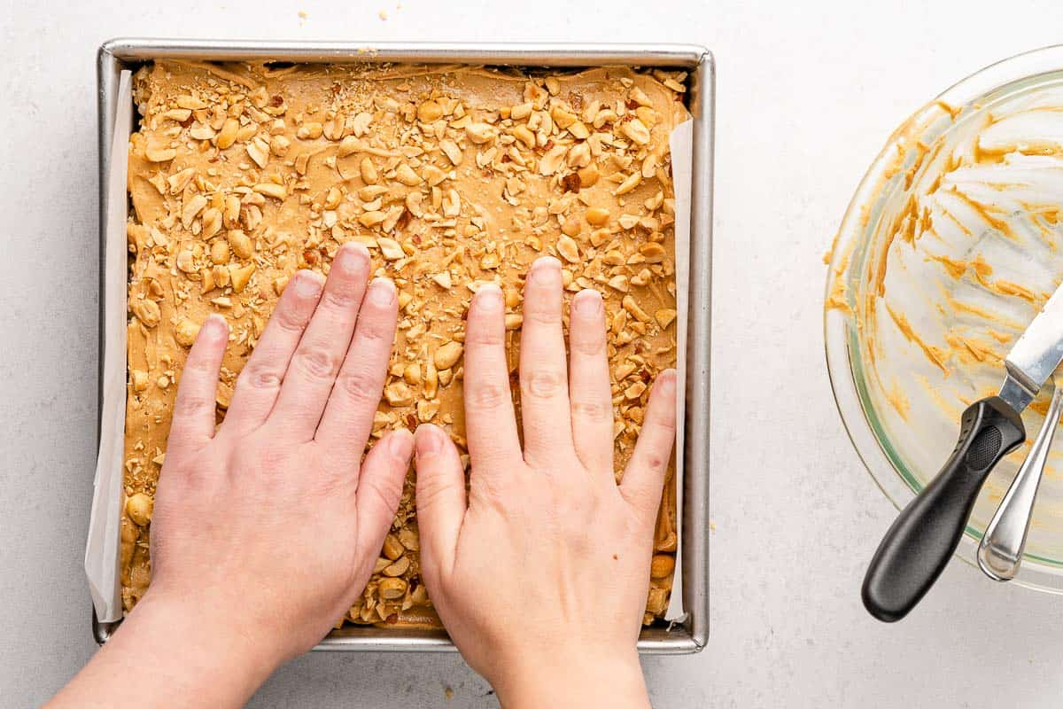 hands pressing chopped peanuts into peanut butter topping