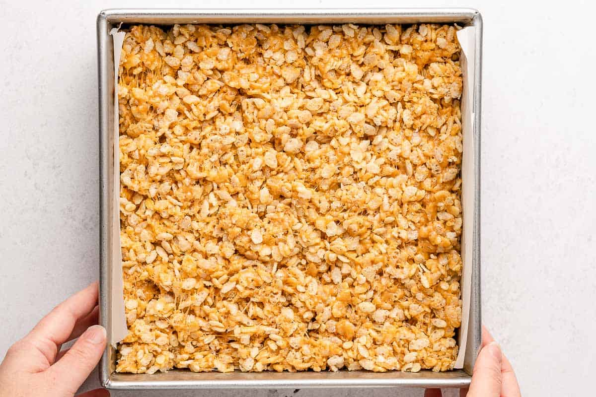 hands holding square pan with rice krispie treats inside