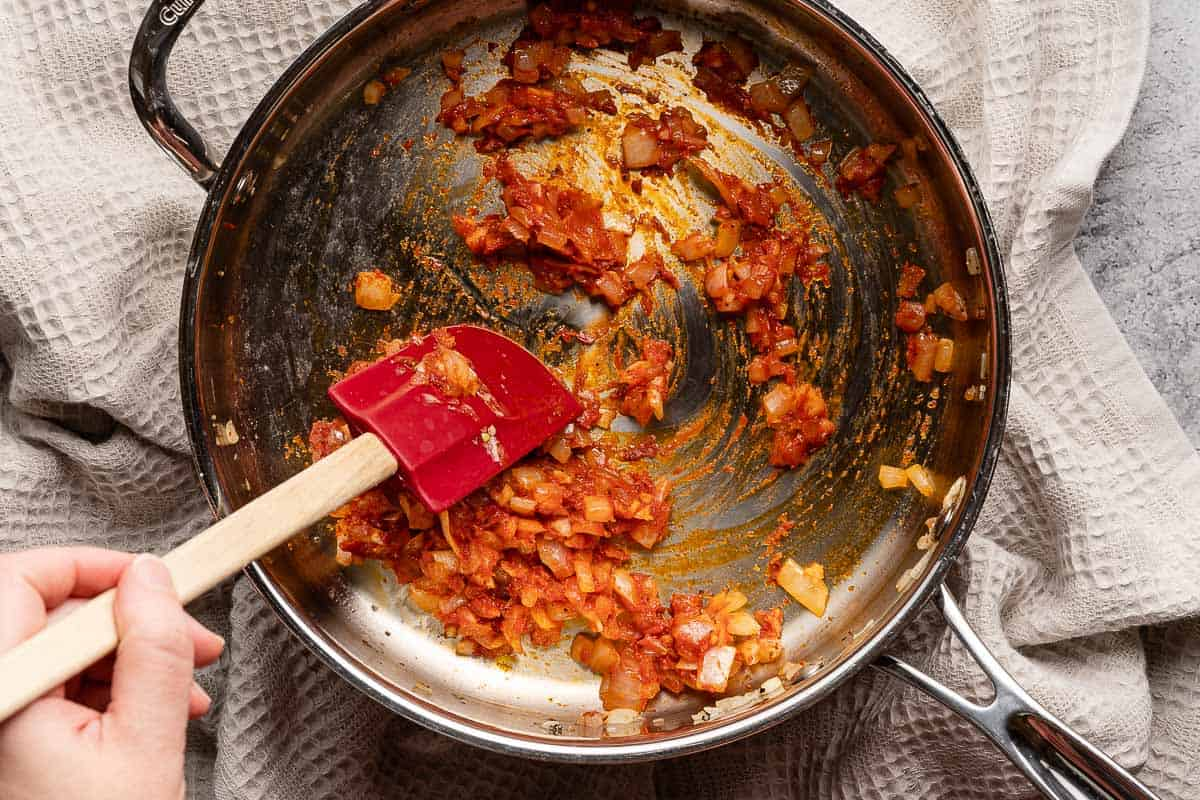 spatula mixing tomato paste with onion and garlic