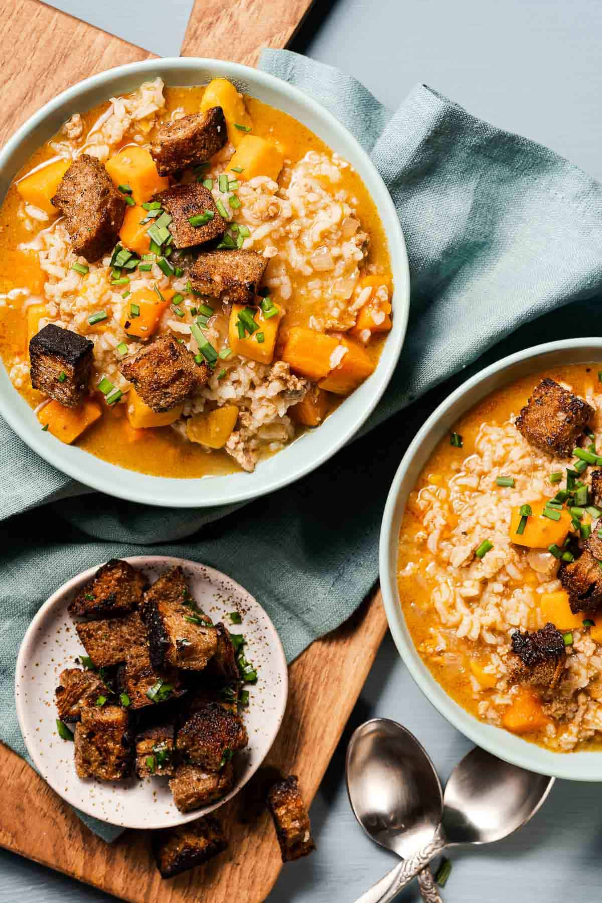 two bowls of turkey sweet potato soup with croutons on the side