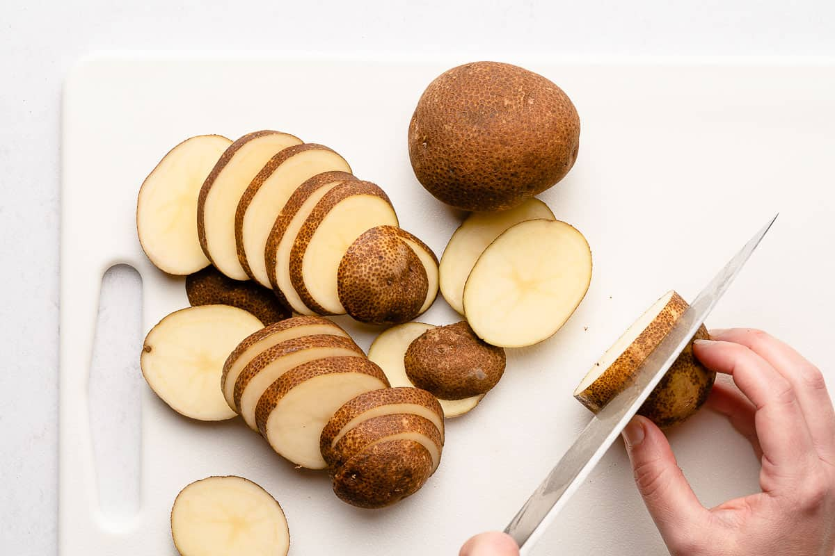 potato being sliced thinly with large knife