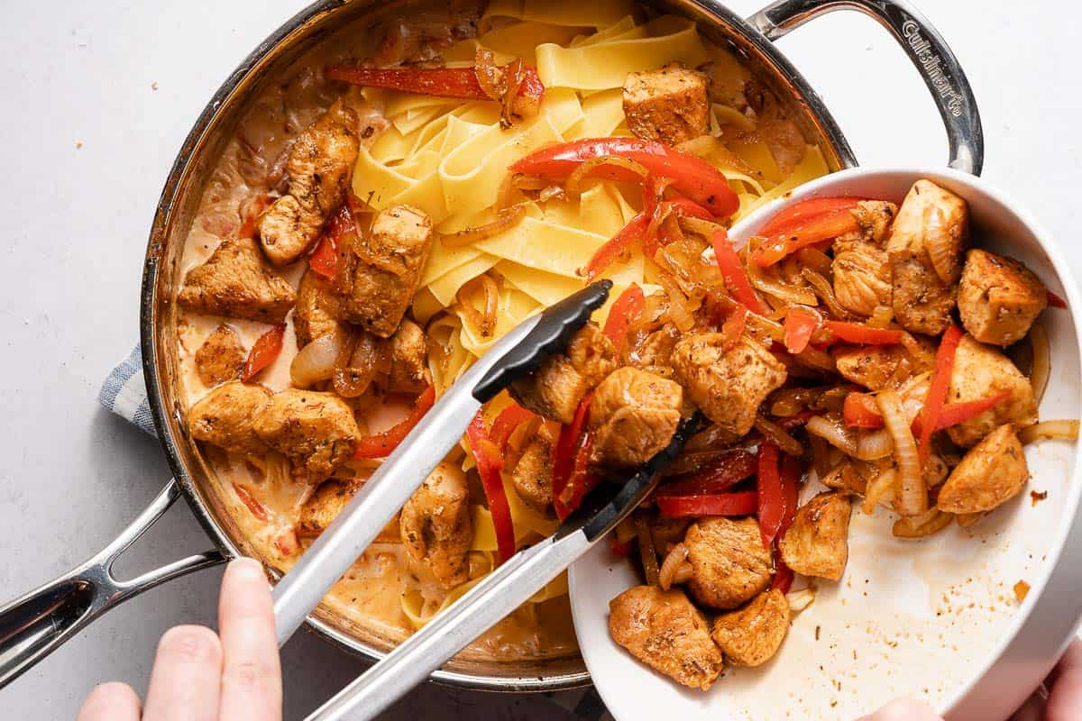 bowl of cooked chicken and vegetables being added into pan with pasta and sauce
