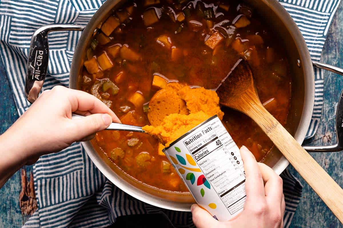 hands scooping pumpkin puree from can into soup pot
