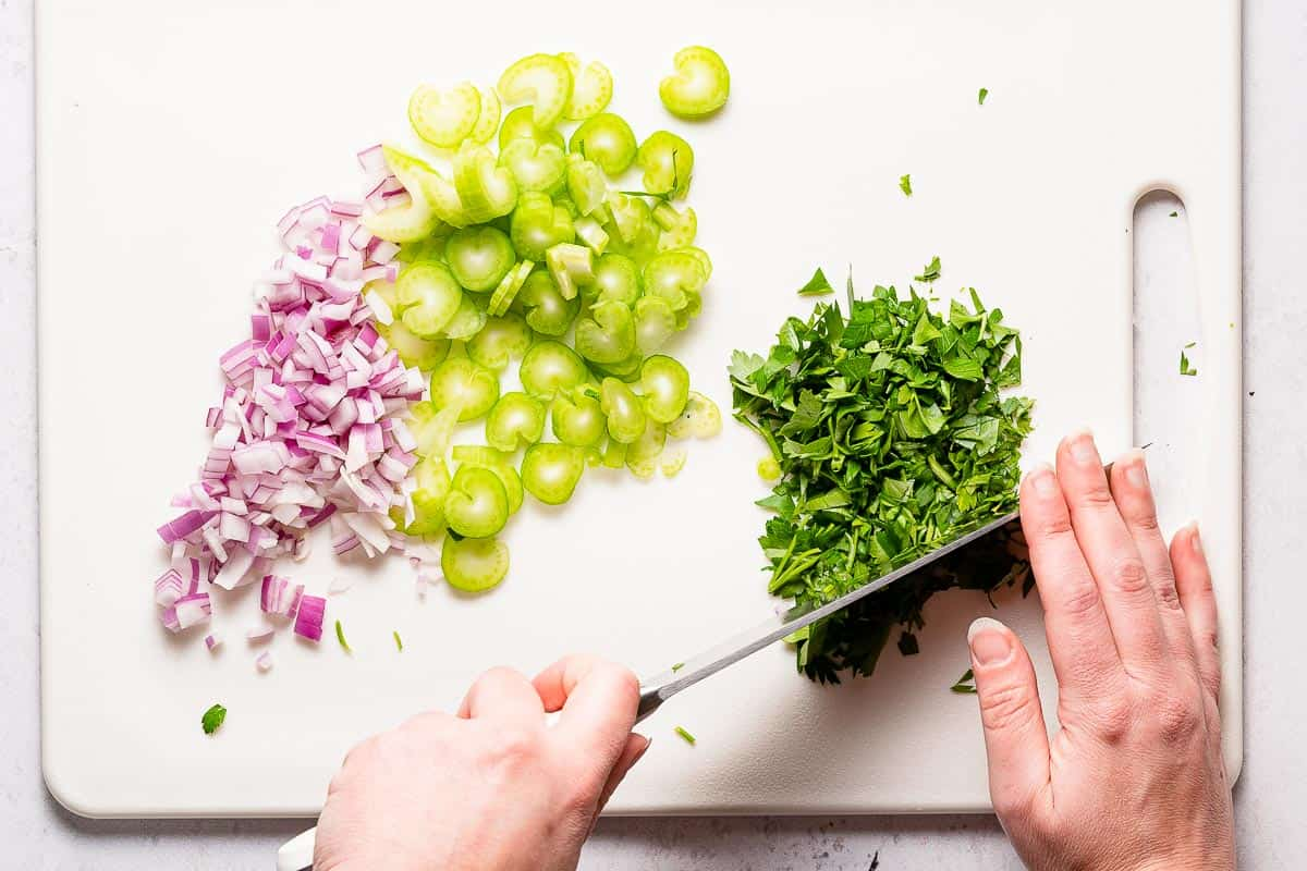 knife chopping parsley with celery and onion on the side