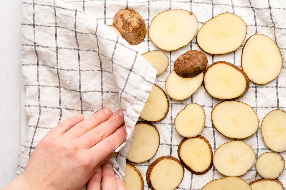 hand blotting sliced potatoes with kitchen towel