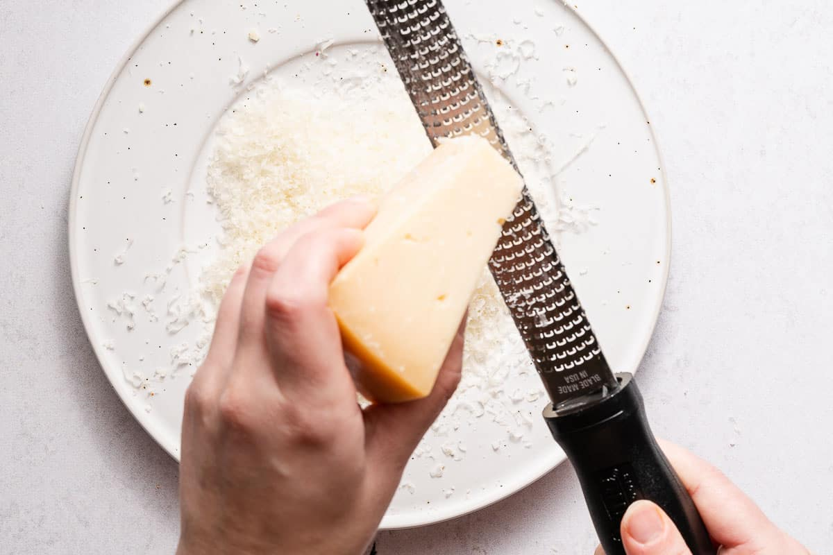 block of Parmesan being grated with microplane