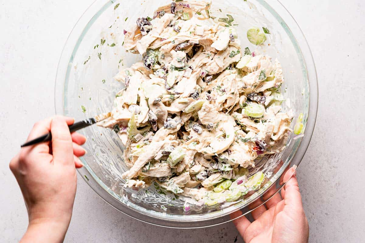 chicken salad being mixed in bowl with spoon