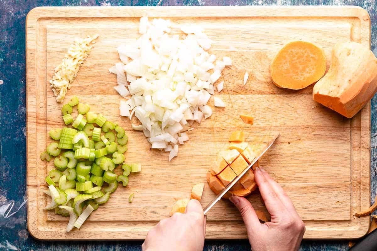chopped celery garlic and onion on cutting board with hands cutting sweet potato into cubes